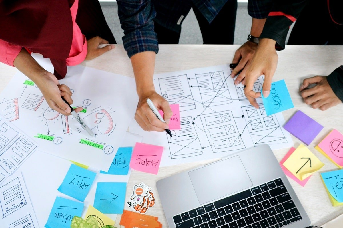 Several individuals participate in a table meeting in which they draw the design thinking process.